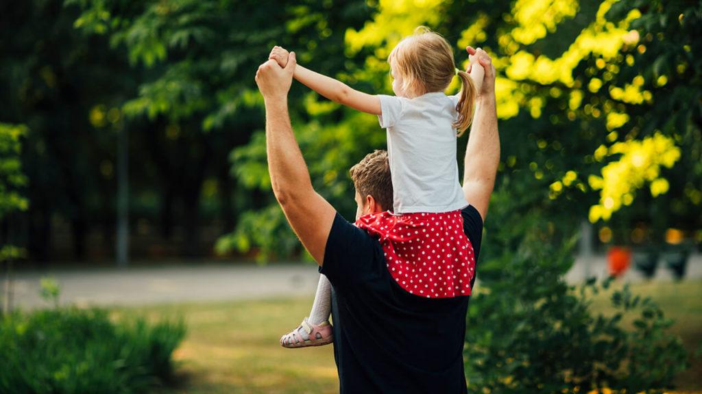 Homem curado da capsulite adesiva carregando a filha acima do ombro