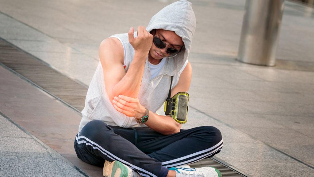 Jovem praticante de parkour com dor no cotovelo por causa da epicondilite