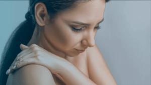 Mulher jovem com dor no ombro por conta da capsulite adesiva