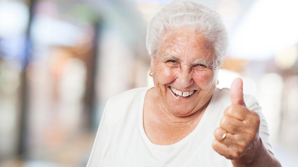 Idosa feliz, fazendo sinal de joia com o polegar depois de fazer um tratamento para artrose no ombro